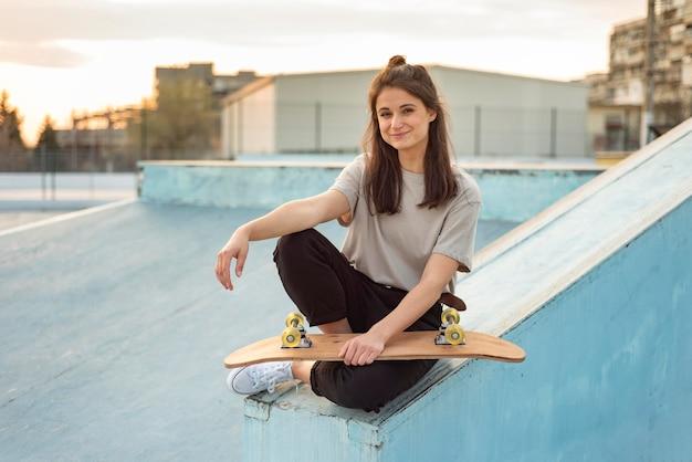 Giovane donna con lo skateboard