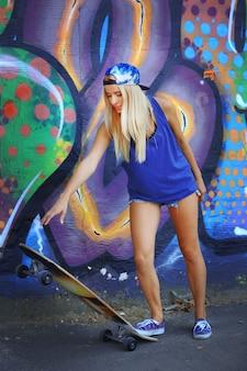 Giovane donna con la tavola da pattinaggio sul fondo dipinto della parete