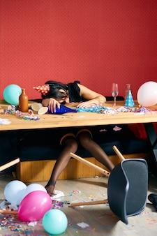 Giovane donna che dorme a tavola in una stanza disordinata dopo la festa di compleanno