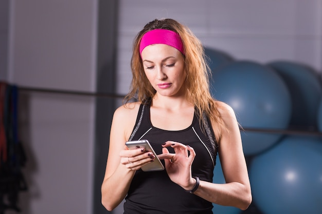 Giovane donna con smartphone e fitness tracker in palestra