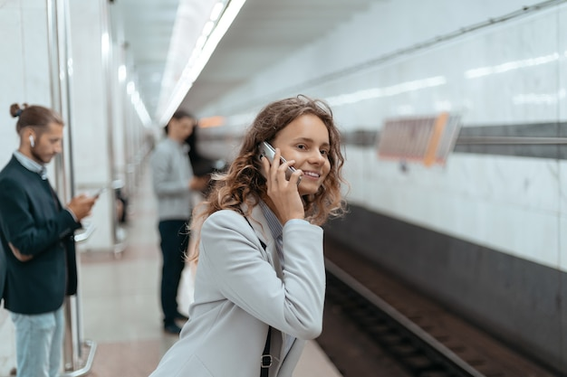 Giovane donna con uno smartphone in piedi sulla piattaforma della metropolitana