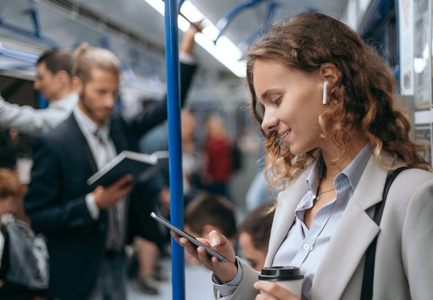 Giovane donna con uno smartphone su un treno della metropolitana