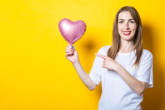 Giovane donna con un sorriso tiene in mano un palloncino a forma di cuore e punta il dito su di esso su uno sfondo giallo. banner.