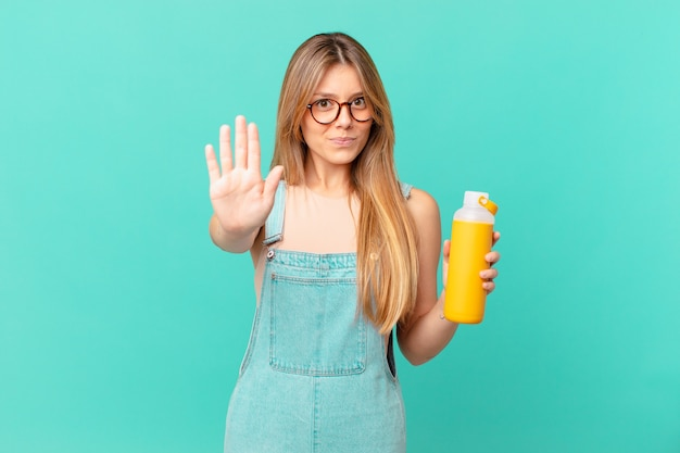 Giovane donna con un frullato dall'aspetto serio che mostra il palmo aperto che fa il gesto di arresto