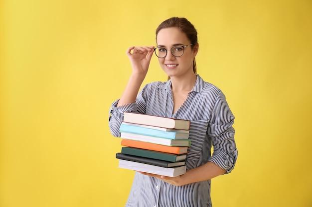 Giovane donna con pila di libri su sfondo colorato