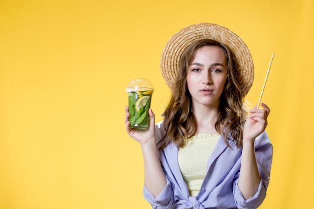 Giovane donna con cappello di paglia tenere cocktail mojito e paglia in una tazza di plastica su sfondo giallo plastic