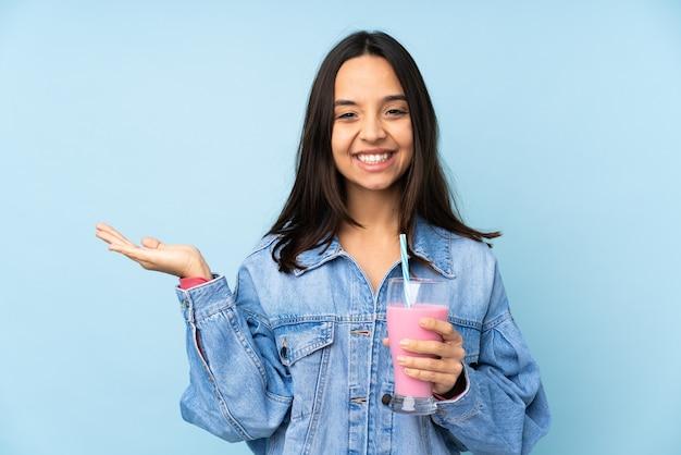 Giovane donna con frappè alla fragola su sfondo blu isolato tenendo copyspace immaginario sul palmo per inserire un annuncio