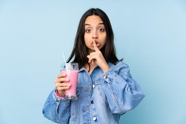 Giovane donna con frullato di fragole su sfondo blu isolato che mostra un segno di silenzio gesto mettendo il dito in bocca