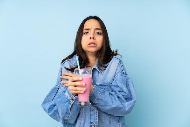 Giovane donna con frappè alla fragola sul congelamento blu isolato