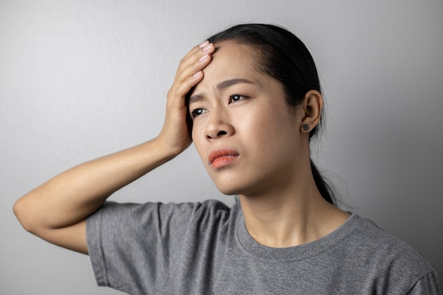 Giovane donna con stress e mal di testa su un grigio.