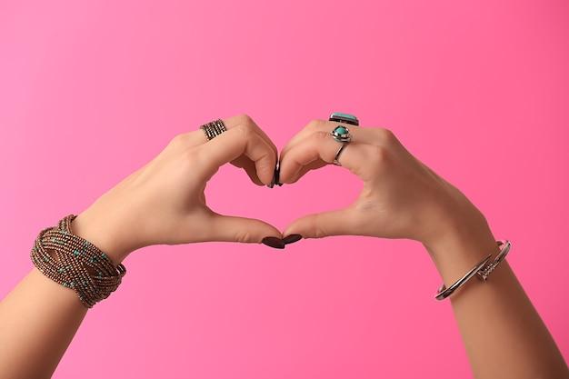 Giovane donna con bigiotteria alla moda che fa il cuore con le sue mani