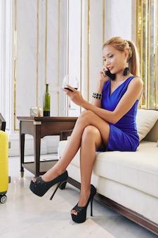 Giovane donna con la valigia che beve vino nella hall dell'hotel e che fa telefonata per ordinare un taxi