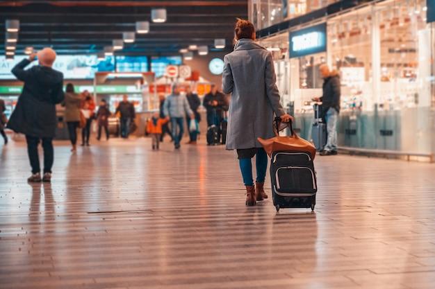 La giovane donna con una valigia alla stazione principale aspetta il suo treno