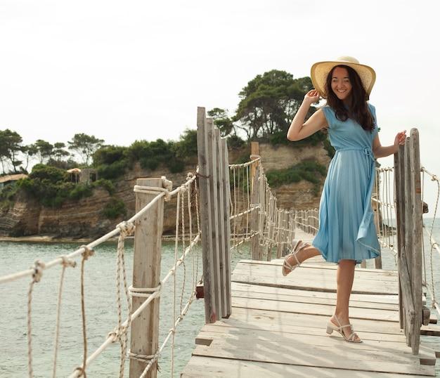 Giovane donna con cappello estivo in posa sul ponte, buone vacanze