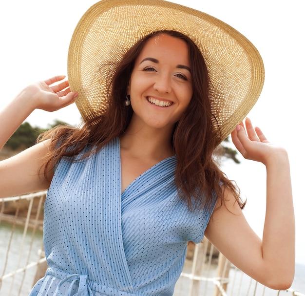 Giovane donna con cappello estivo in posa sul ponte, felice vacanza