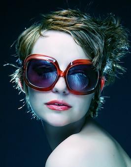 Giovane donna con occhiali da sole su sfondo nero