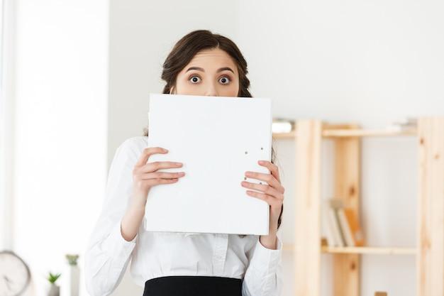 Giovane donna con gli occhi sorpresi che dà una occhiata fuori da dietro il manifesto di carta. donna di affari che tiene grande insegna bianca in ufficio moderno.