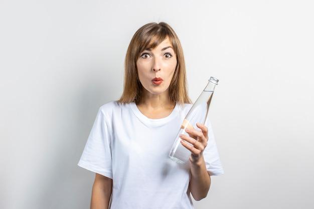La giovane donna con una faccia sorpresa tiene una bottiglia di acqua limpida su una superficie chiara