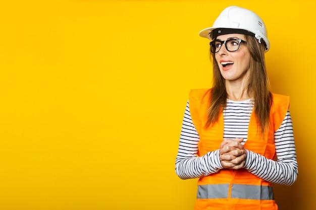 Giovane donna con una faccia sorpresa in un giubbotto e un elmetto su uno sfondo giallo. concetto di costruzione, nuova costruzione. bandiera.