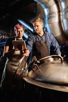 Giovane donna con tablet che scorre l'elenco delle fasi di lavorazione della birra e lo mostra al suo collega maschio utilizzando attrezzature speciali
