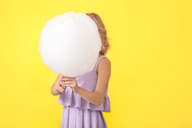 Giovane donna con gustoso zucchero filato sul colore