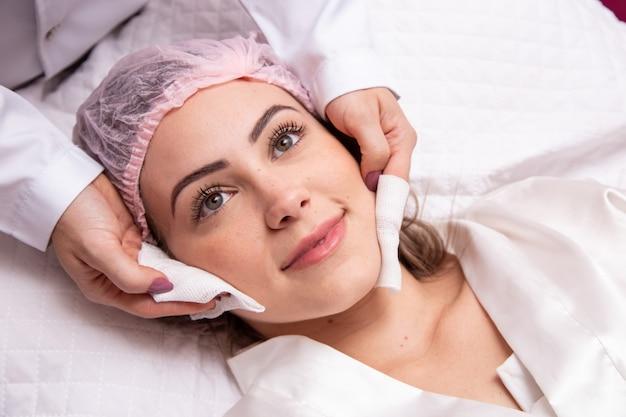 Giovane donna con sopracciglia folte e pelle perfetta su sfondo pulito, concetto fotografico di bellezza, cura della pelle, concetto spa, trattamento, massaggio facciale.