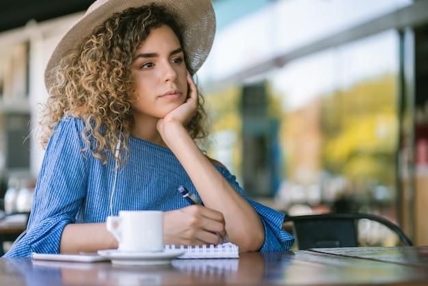 Giovane donna con un'espressione premurosa sul viso mentre scrive su un taccuino in una caffetteria.
