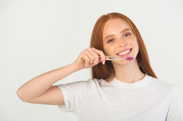 Giovane donna con uno spazzolino da denti in mano