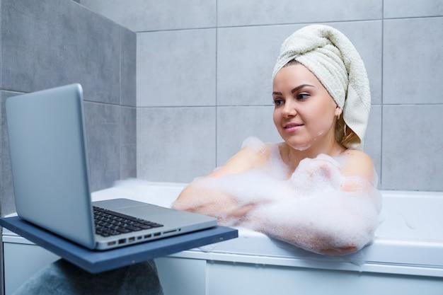 Una giovane donna con un asciugamano in testa sta guardando un film su un laptop mentre è seduta in una vasca da bagno in un salone di bellezza. rilassati in bagno senza biancheria. cura del corpo e concetto di relax.