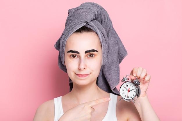 Giovane donna con un asciugamano in testa dipinge le sopracciglia da sola e con in mano una sveglia. concept spa day a casa e in quarantena