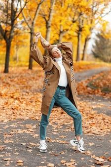 Giovane donna con un taglio di capelli alla moda in un cappotto elegante pone all'aperto in un parco