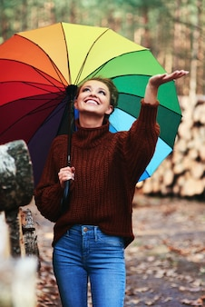 Giovane donna con ombrello nella foresta autunnale