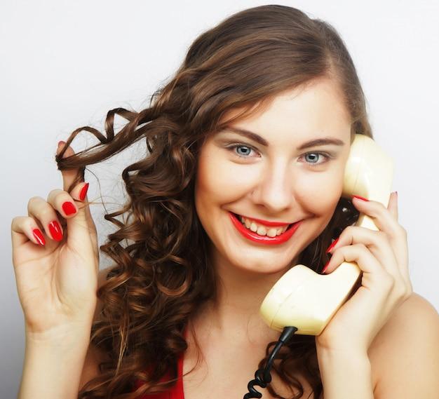Giovane donna con telefono vintage.