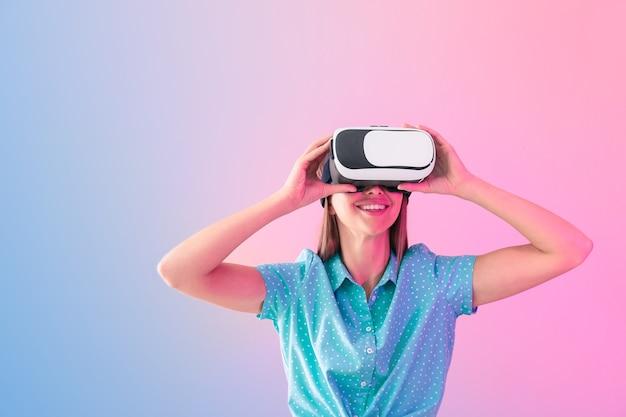 Giovane donna con occhiali per realtà virtuale su sfondo colorato