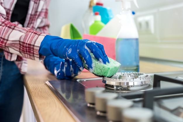 Giovane donna con detersivo liquido e straccio lava e pulisce in cucina. concetto di pulizia.