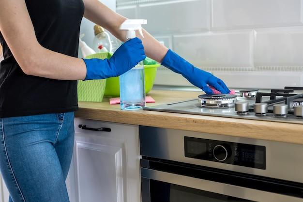 Giovane donna con detersivo liquido e straccio lava e pulisce in cucina