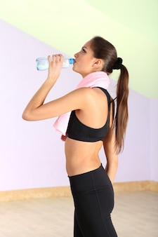 Giovane donna con acqua dopo l'allenamento in palestra