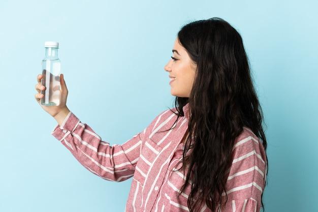 Giovane donna con un'acqua isolata sulla parete blu con l'espressione felice
