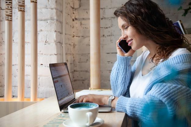 Giovane donna con capelli ondulati in caldo maglione lavorato a maglia blu sta parlando al telefono e scrivendo note mentre beve un sano latte caldo caffè blu a base di tè di pisello farfalla naturale. bellezza e benessere
