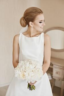 Una giovane donna con acconciatura da sposa in abito da sposa bianco satinato in posa con bouquet di fiori bianchi nelle sue mani all'interno