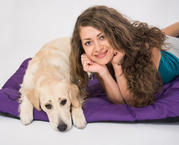 Giovane donna con un golden retriever cucciolo bianco