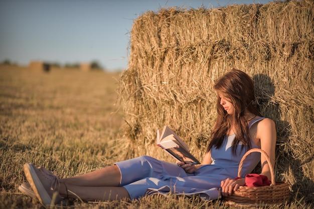 Una giovane donna con un cesto di vimini è seduta in un campo appoggiata a un pagliaio e legge un libro