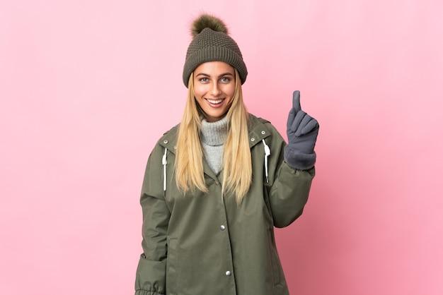 Giovane donna con cappello invernale isolato sul muro rosa rivolto verso l'alto una grande idea