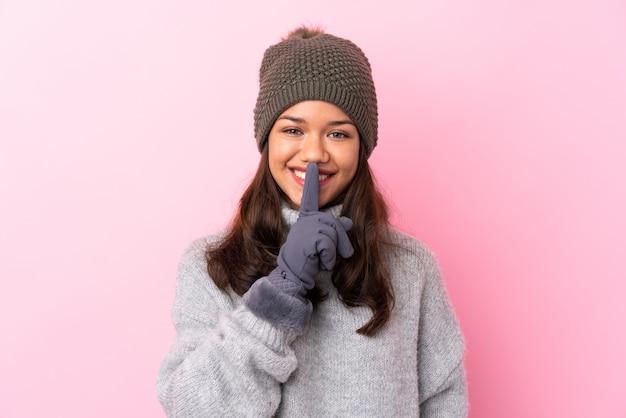 Giovane donna con cappello invernale su muro isolato