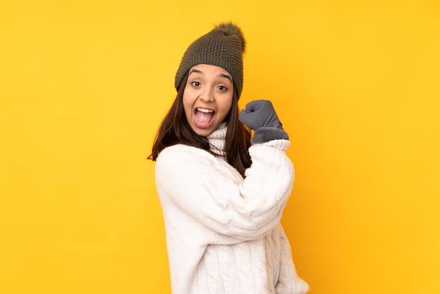 Giovane donna con cappello invernale su sfondo giallo isolato che celebra una vittoria