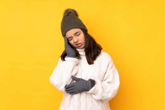 Giovane donna con cappello invernale su sfondo giallo isolato con mal di testa