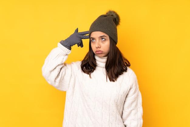 Giovane donna con cappello invernale su sfondo giallo isolato con problemi che fanno gesto di suicidio