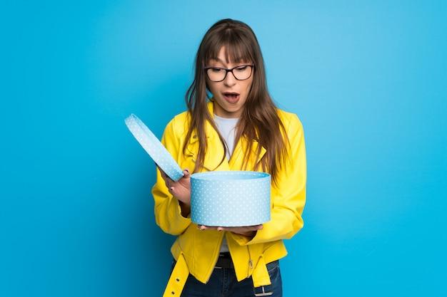 Giovane donna con giacca gialla sulla parete blu con un regalo in mano