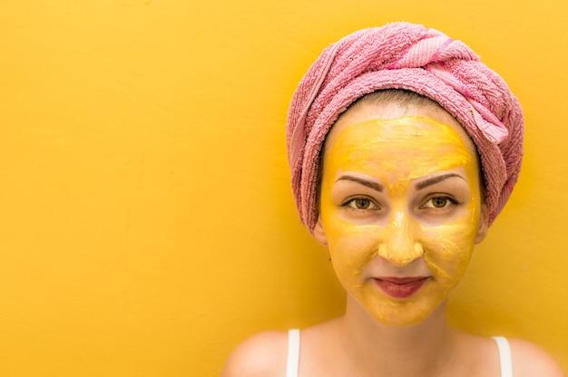 Giovane donna con una maschera gialla sul viso e un asciugamano rosa in testa.