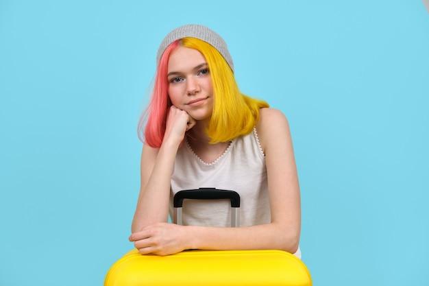 Giovane donna con valigia gialla, sorridente ragazza adolescente hipster con capelli tinti colorati, guardando la fotocamera. sfondo blu studio. turismo, viaggi, stile di vita, studenti, concetto in movimento Foto Premium